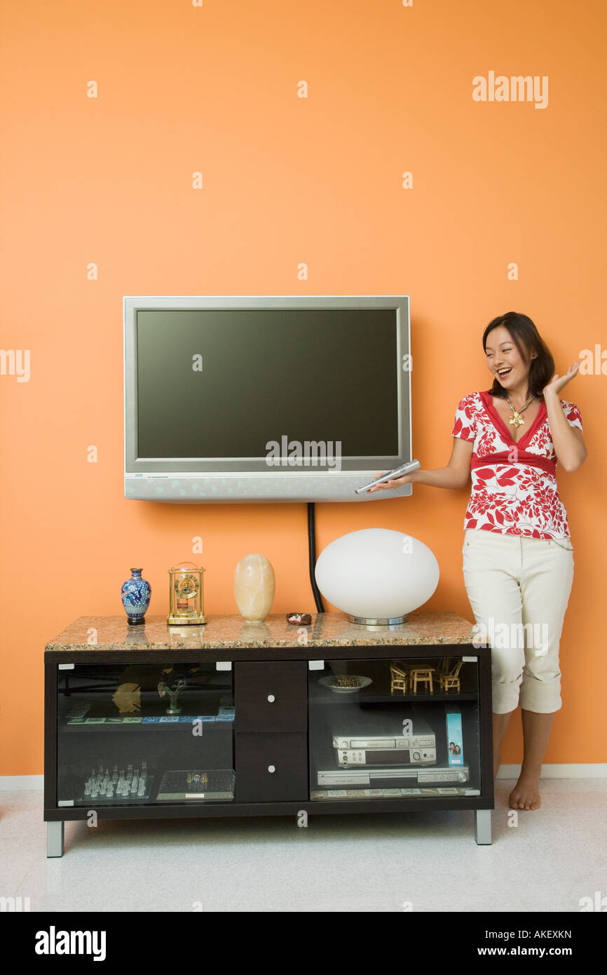 Young woman holding a remote control and standing near a cabinet - Stock Image