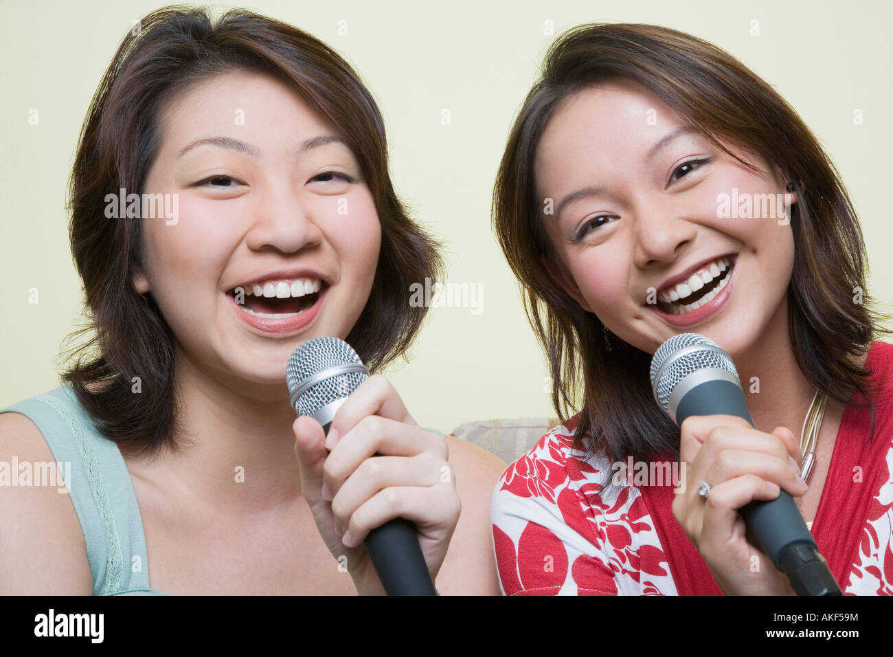 Portrait of two young women singing together into microphones - Stock Image