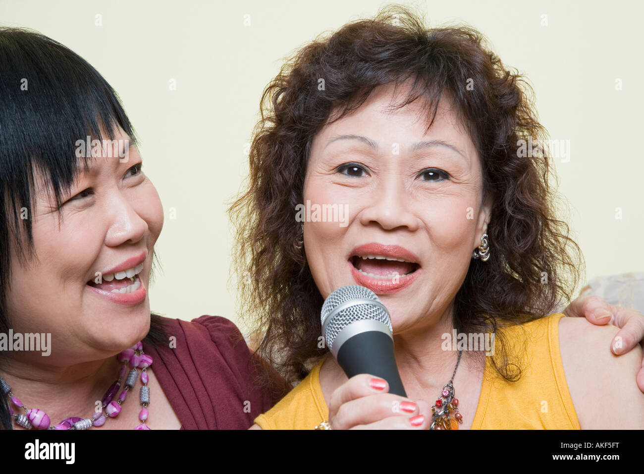 Portrait of a senior woman singing with a mature woman in front of a microphone - Stock Image