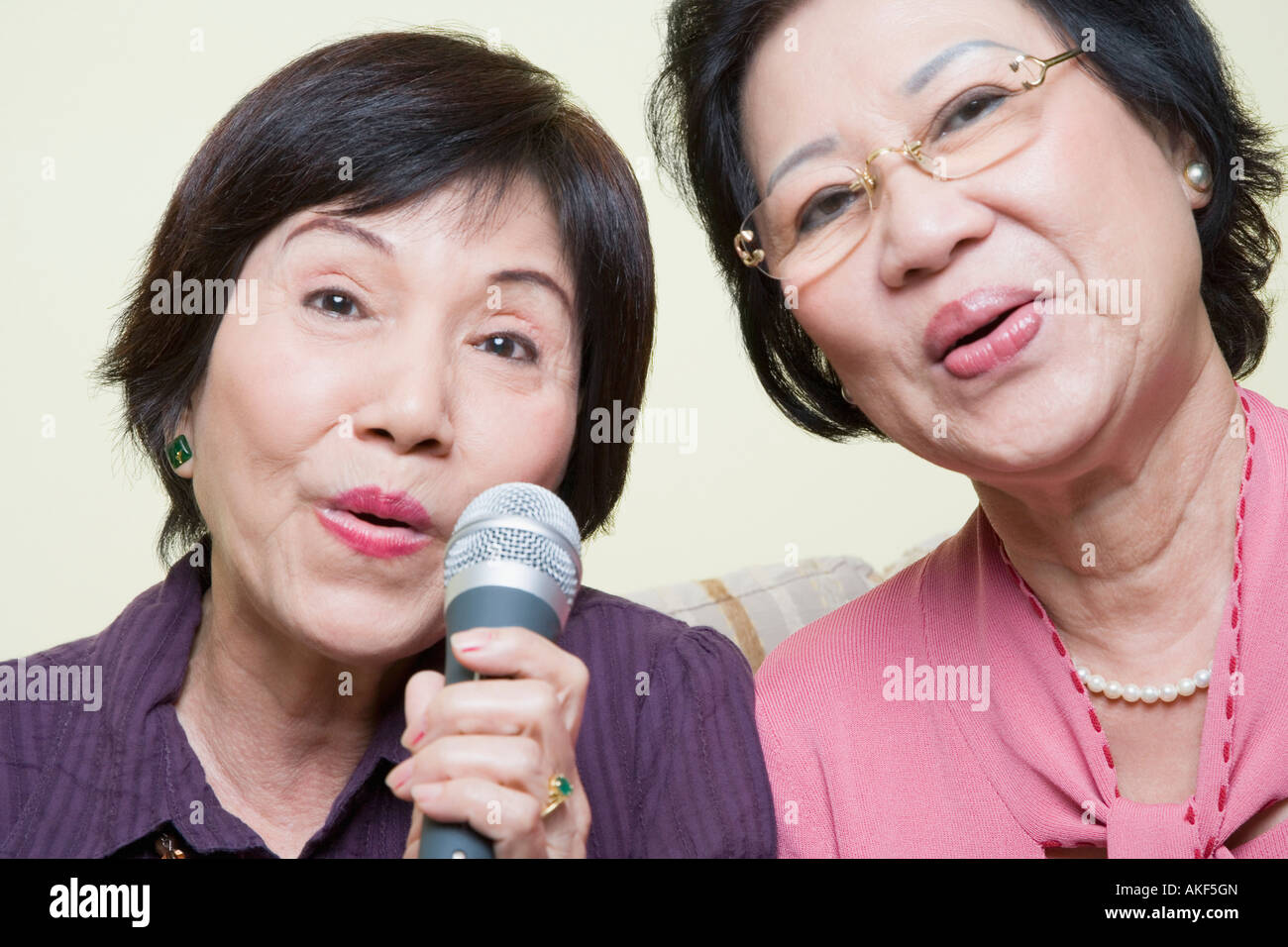 Portrait of two senior women singing into a microphone - Stock Image