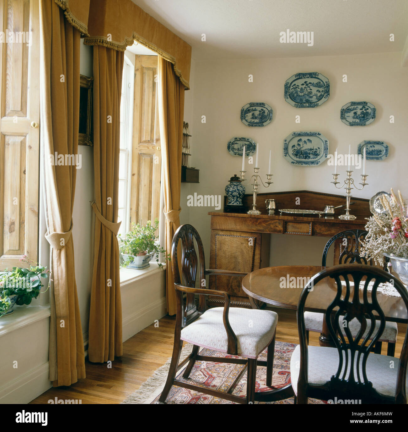 Blue And White Plates Above Antique Sideboard In Country Dining Room With Gold Velvet Curtains Wooden Shutters