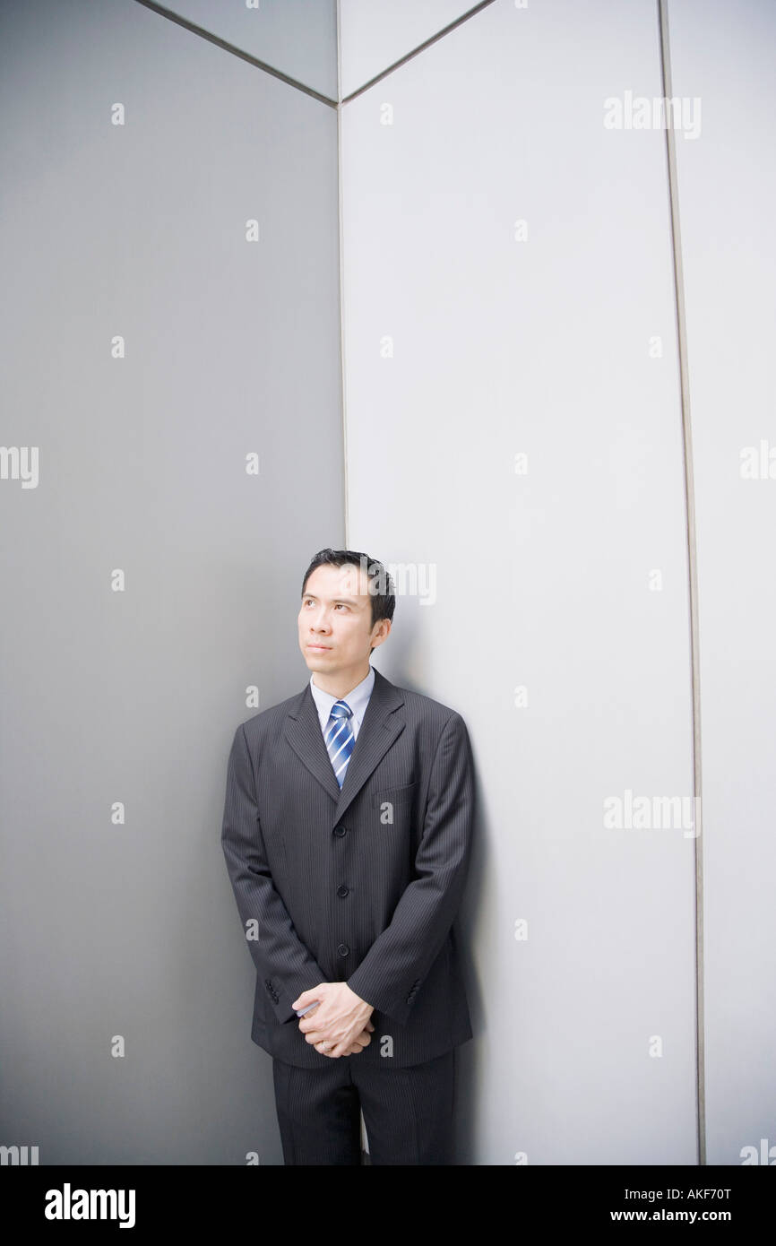 Businessman standing in a corner with his hands clasped - Stock Image