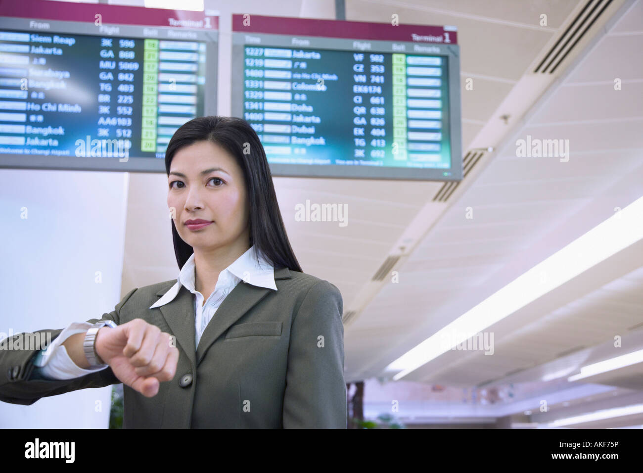 Portrait of a businesswoman in front of an airport departure board - Stock Image