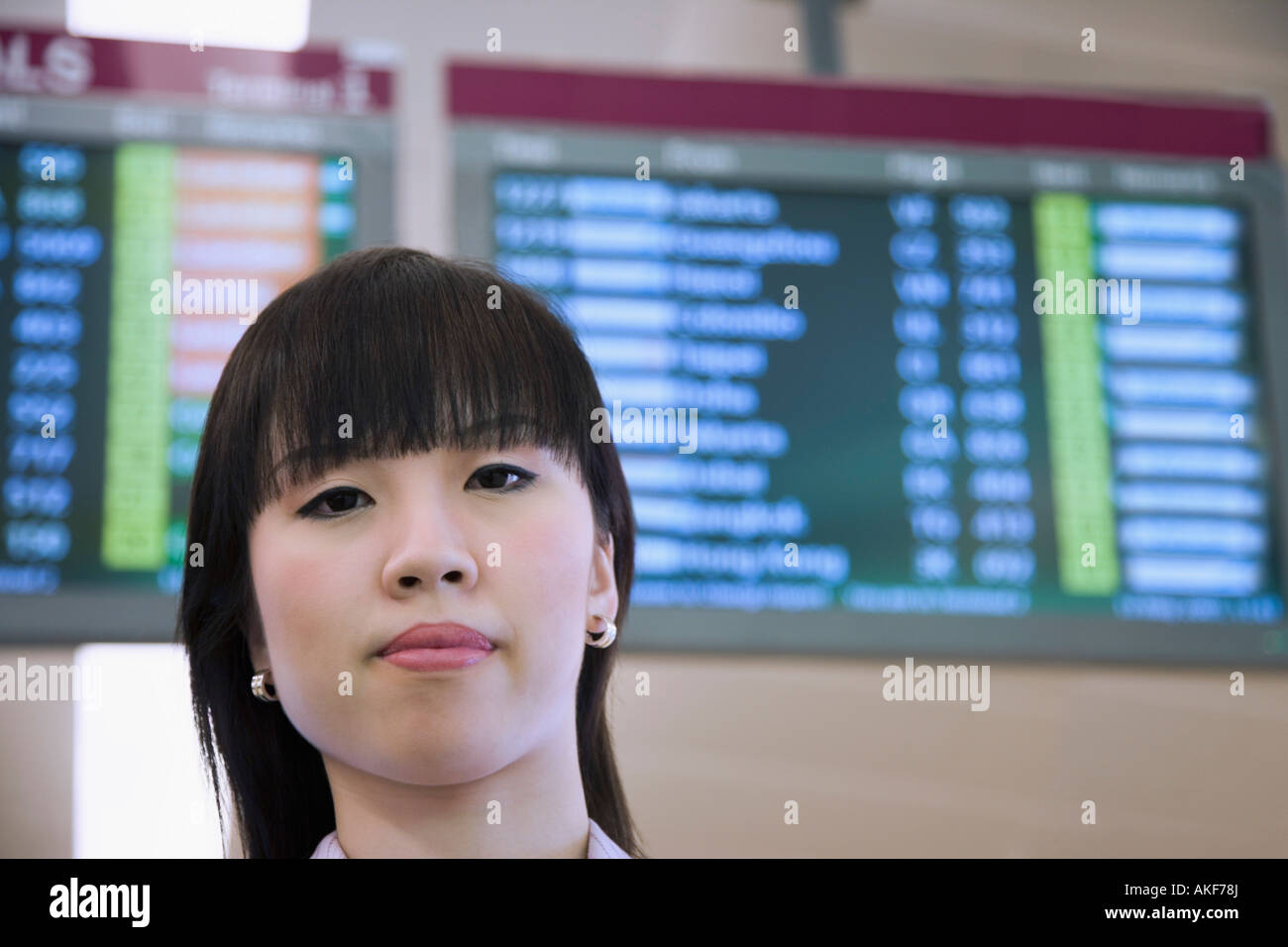 Portrait of a businesswoman in front of an arrival departure board - Stock Image