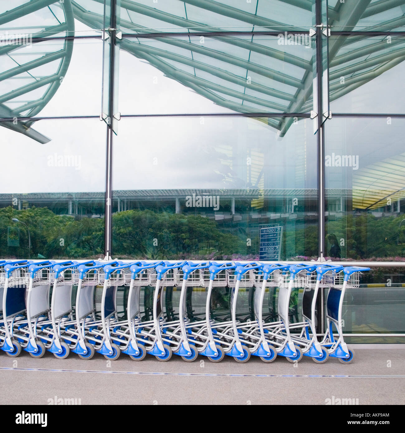 Luggage carts in a row outside an airport - Stock Image