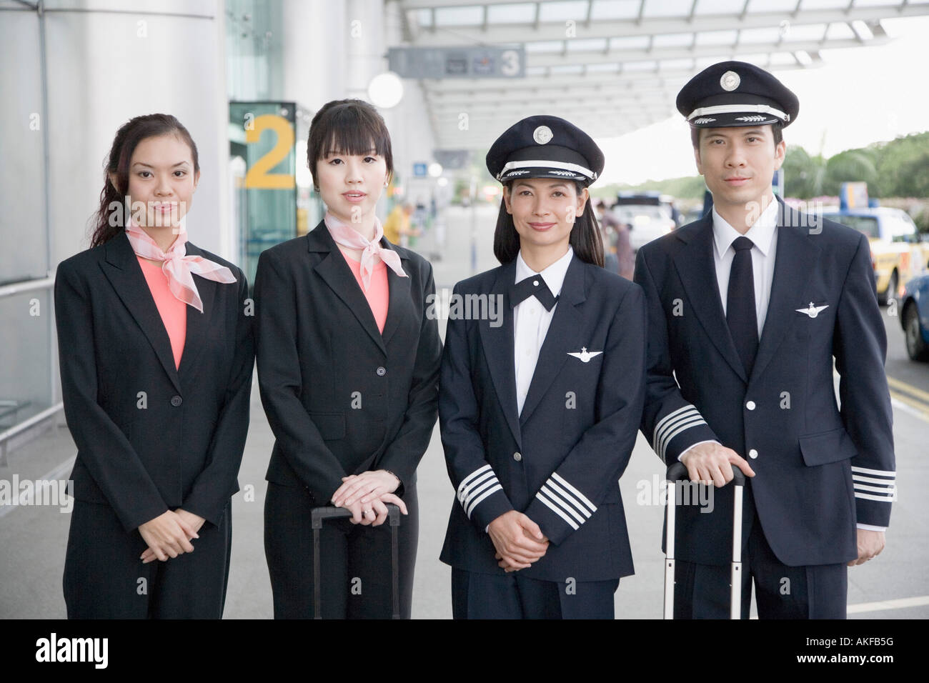 Portrait of a male and a female pilot standing with two cabin crew members - Stock Image