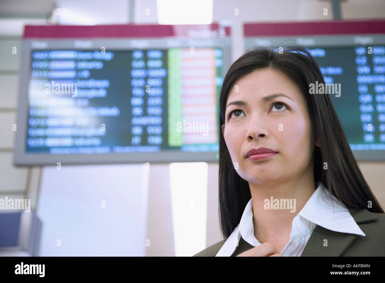 Low angle view of a businesswoman in front of an arrival departure board - Stock Image