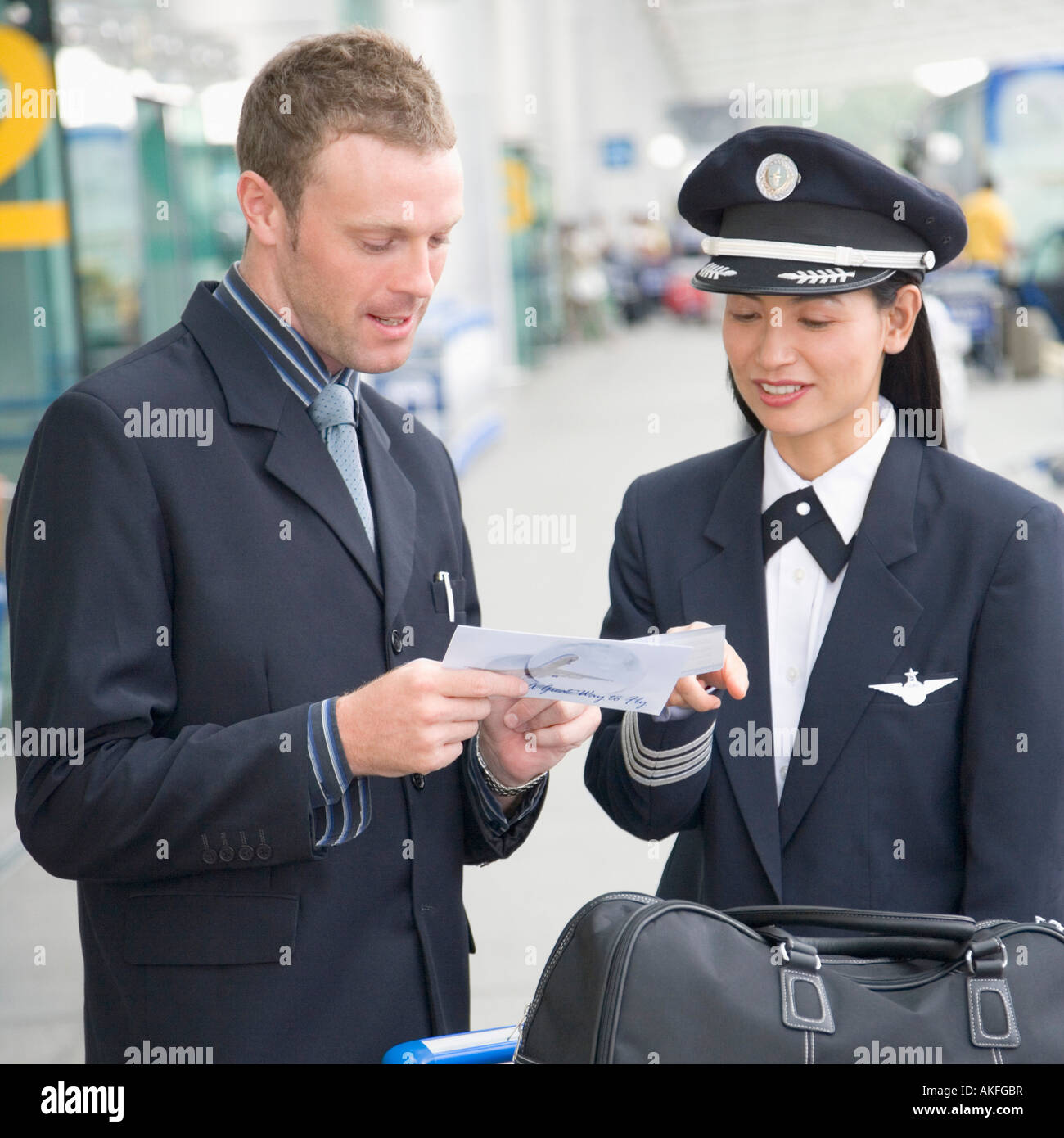 Businessman showing an airplane ticket to a female pilot Stock Photo