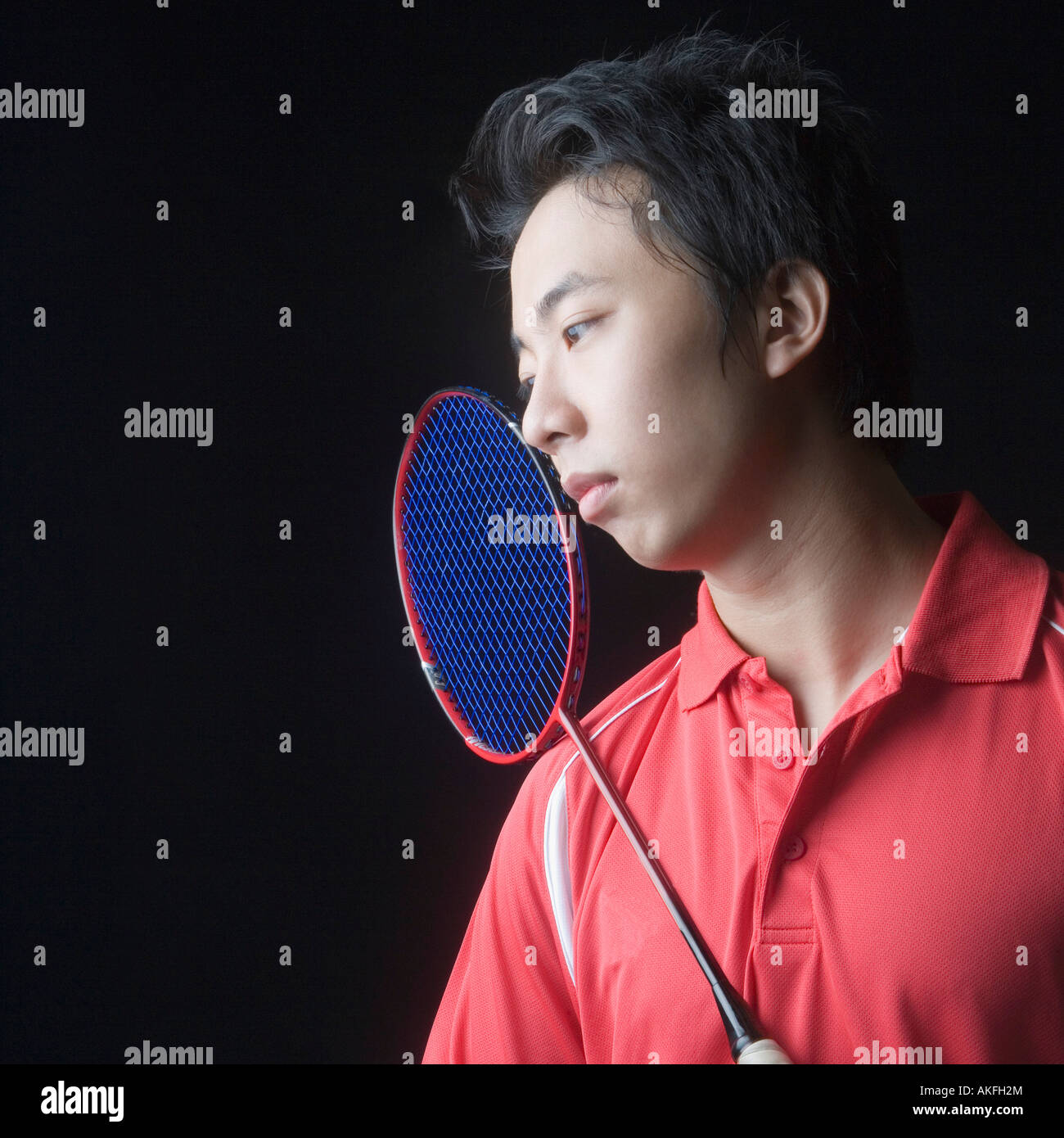 Close-up of a young man with a badminton racket - Stock Image
