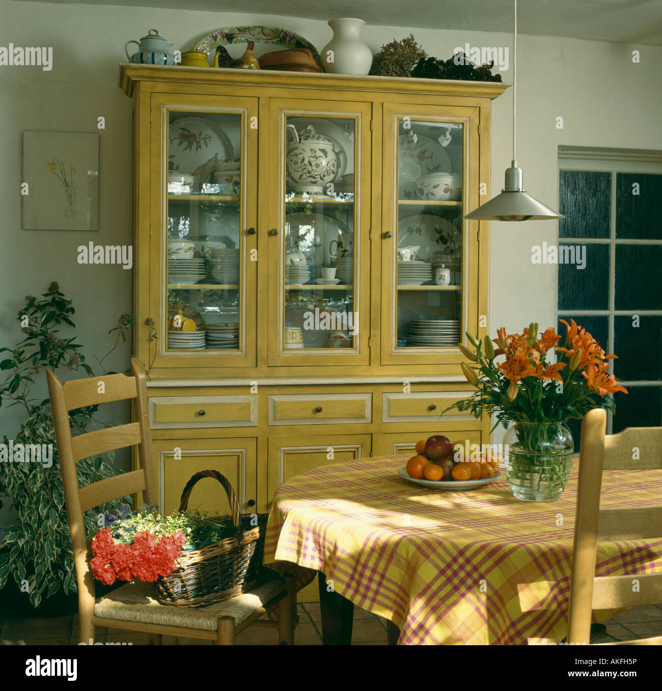 Painted yellow dresser with glass doors in dining room with ...