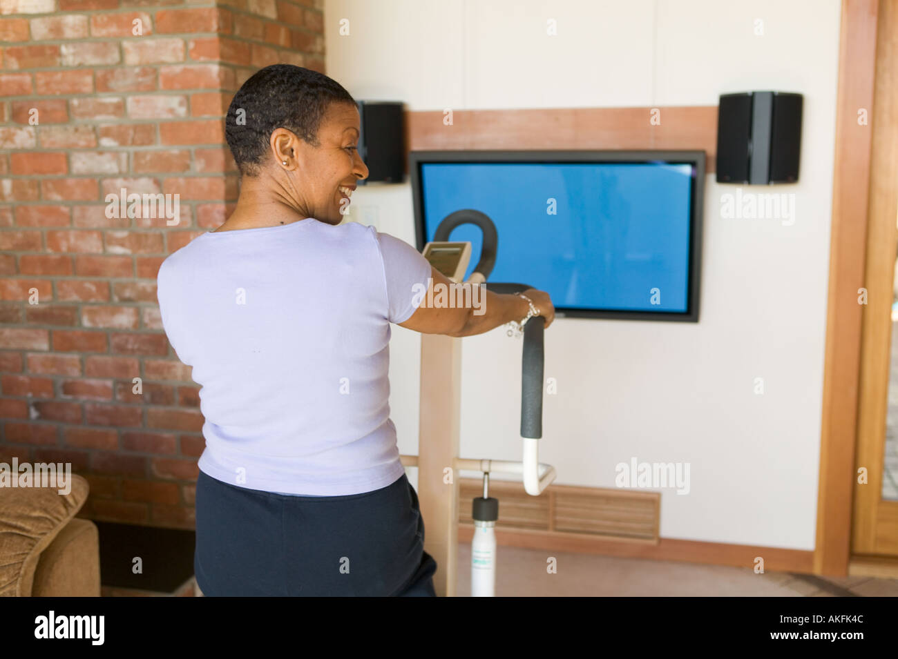 Senior African American exercising on stepper machine and plasma TV - Stock Image