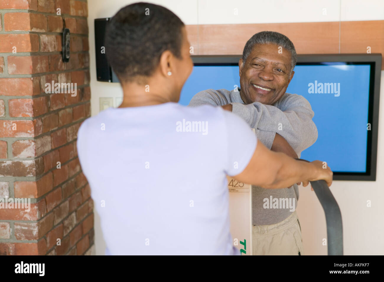 Seniors African Americans Exercising on stepper machine and plasma TV - Stock Image