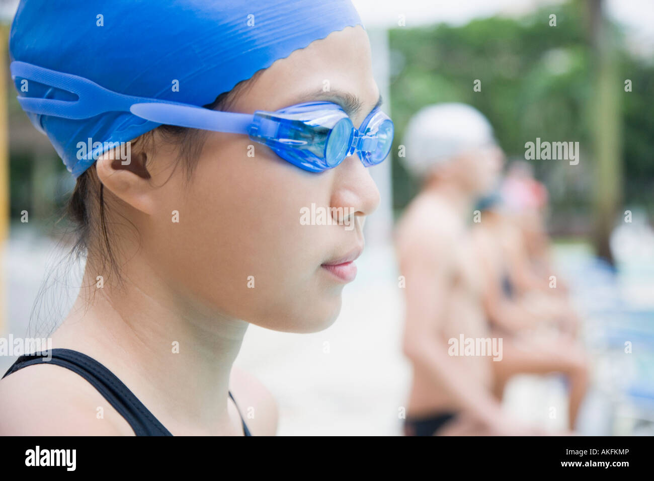 Close-up of a young woman wearing swimming goggles and standing at a poolside - Stock Image