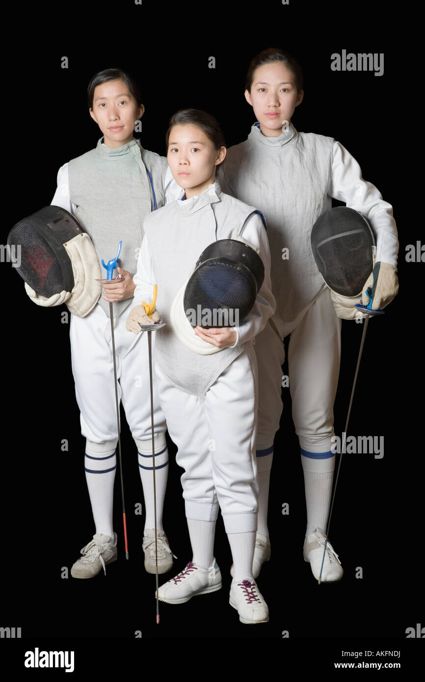 Portrait of three female fencers holding fencing masks and fencing foils - Stock Image