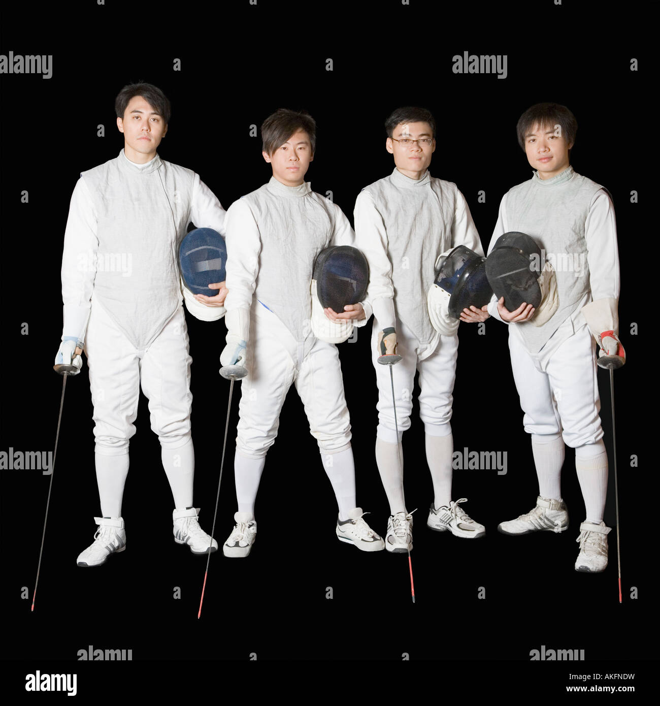 Portrait of four male fencers holding fencing foils and fencing masks - Stock Image