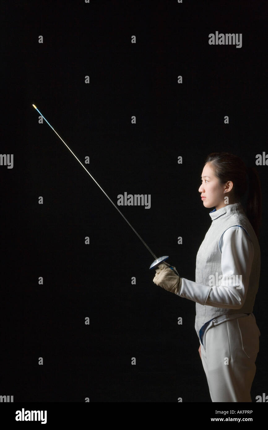 Side profile of a female fencer holding a fencing foil Stock Photo
