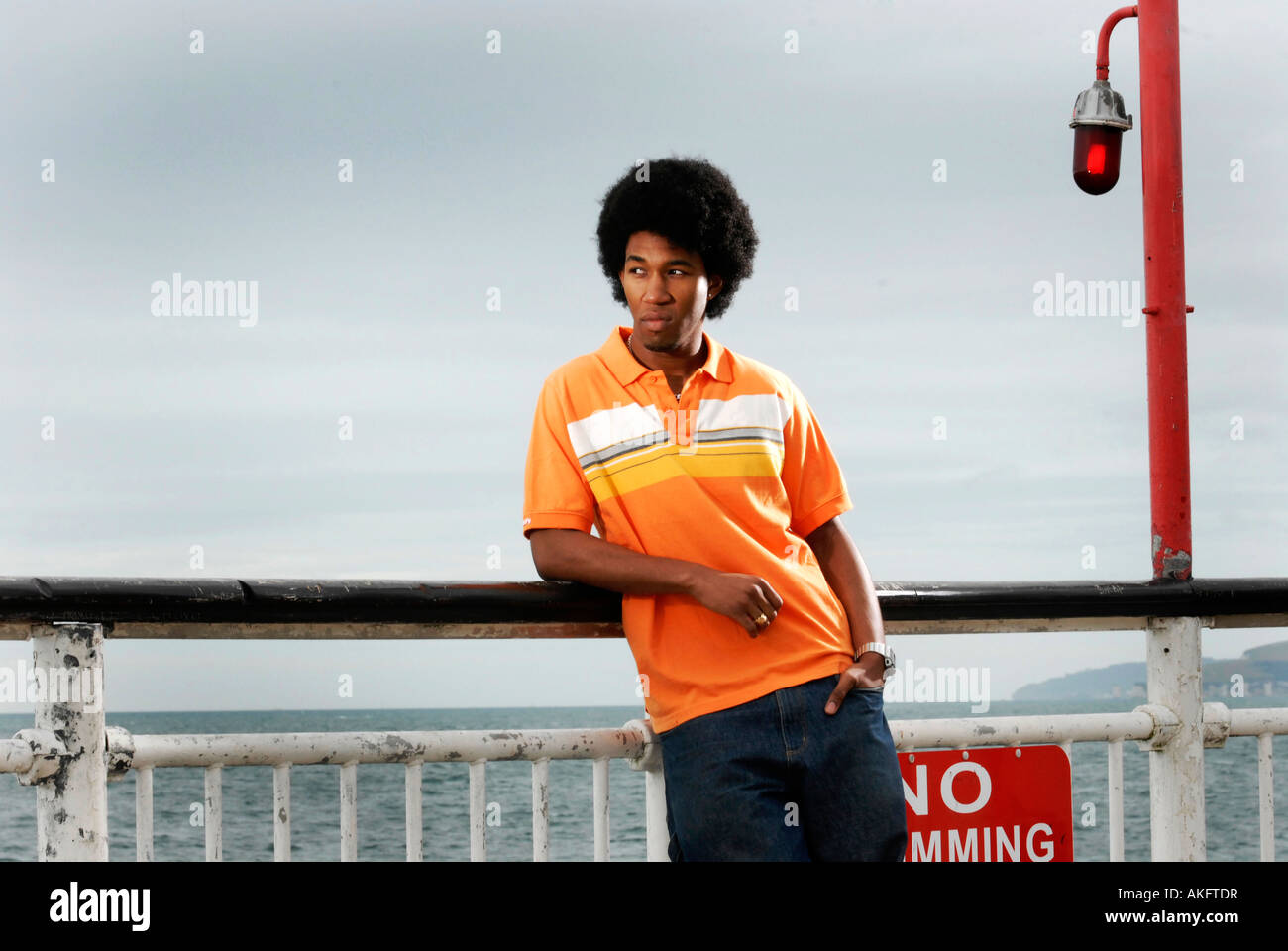 A young cool black man leaning against a rail at the end of Bournemouth Pier with a red light next to him. - Stock Image