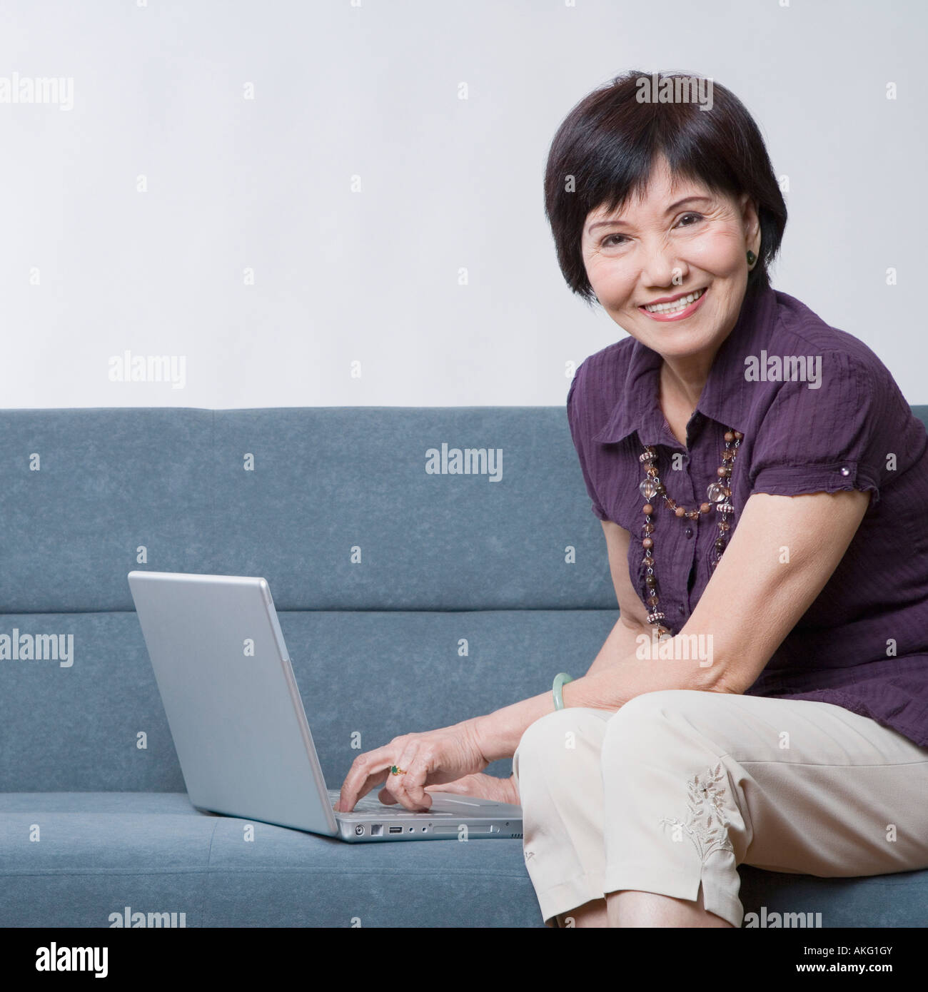 Portrait of a senior woman using a laptop and smiling - Stock Image