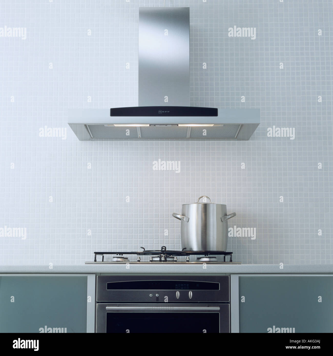 Stainless steel extractor fan above pan on hob in modern kitchen ...