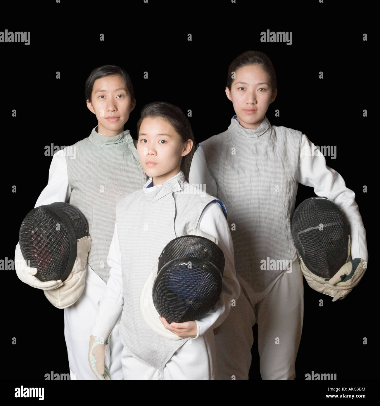 Portrait of three female fencers holding fencing masks - Stock Image