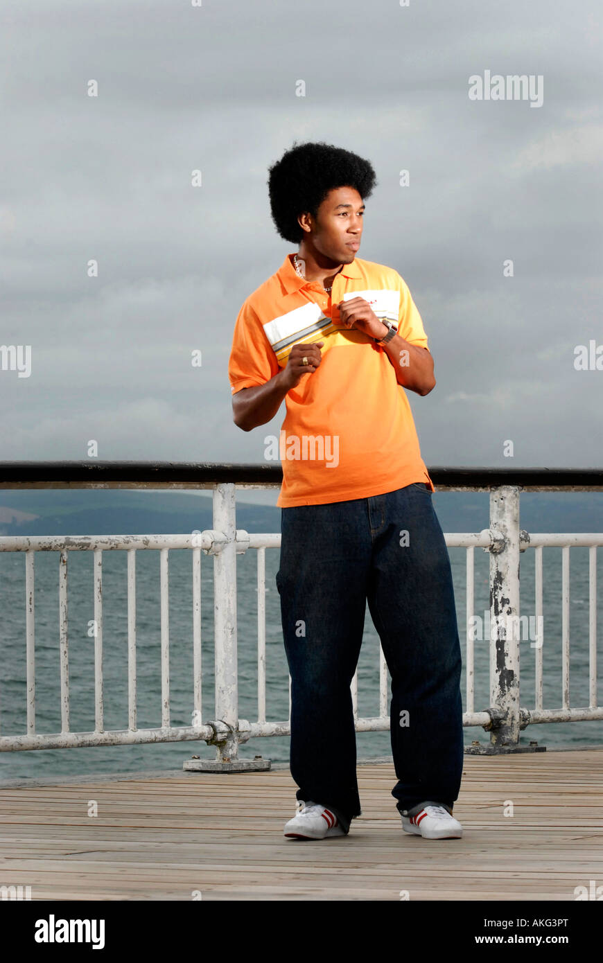 A young cool black man dancing at the end of Bournemouth Pier with the sea behind him. - Stock Image