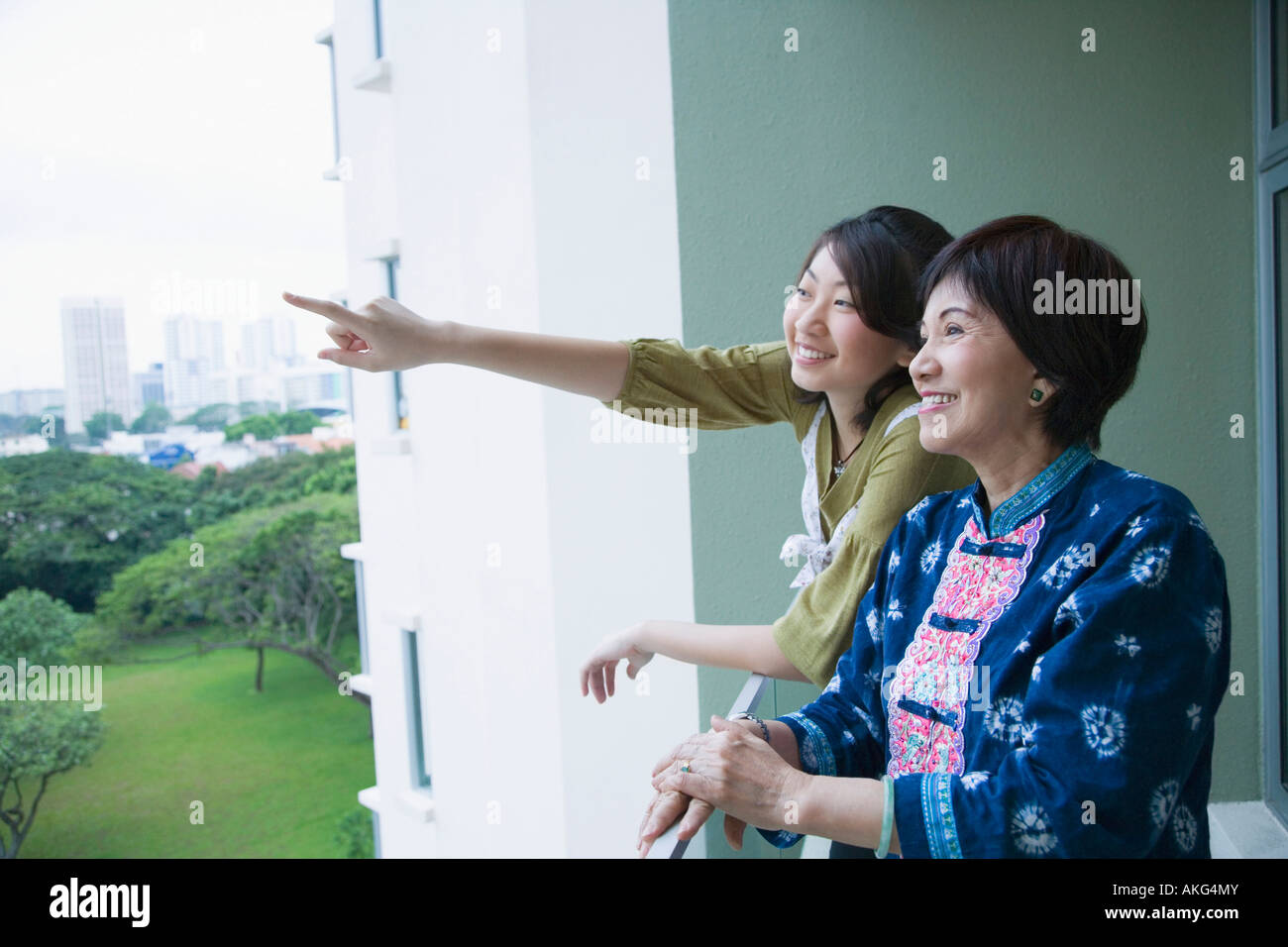 Side profile of a senior woman standing in a balcony with her granddaughter - Stock Image