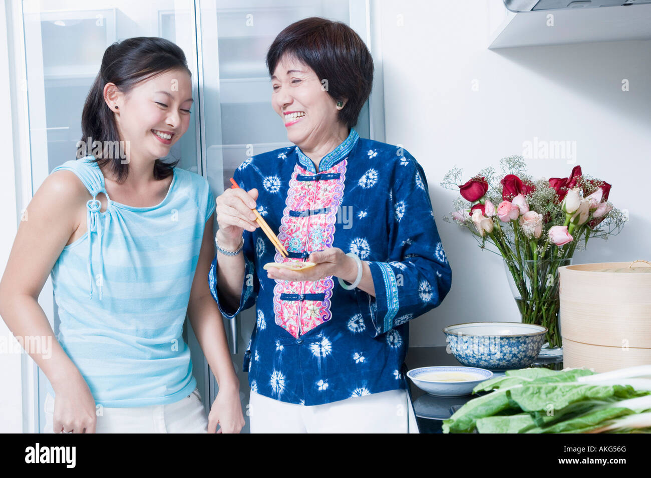 Senior woman preparing food with her granddaughter standing beside her and smiling - Stock Image
