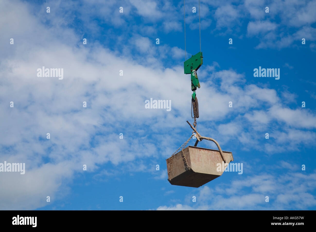 Crane bucket suspended by wires in mid-air against blue sky - Stock Image