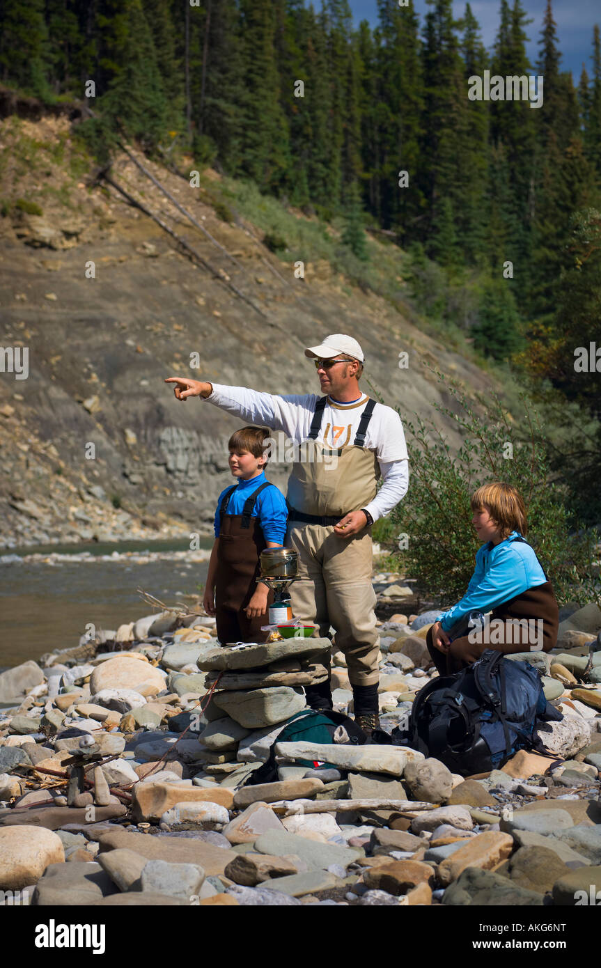 Father and sons on river shoreline - Stock Image