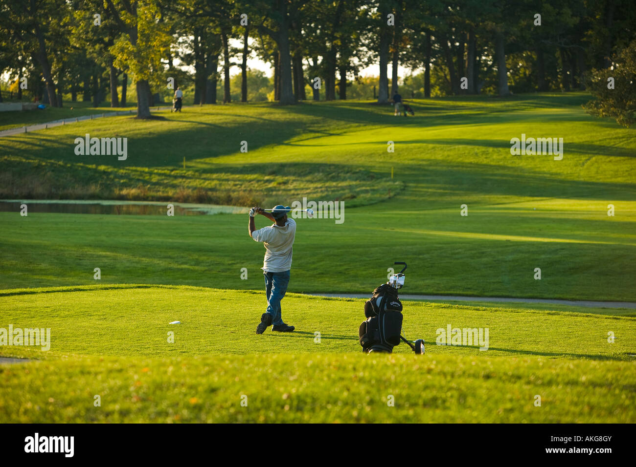 ILLINOIS Aurora Male golfer tee off at Philips Park public golf course club behind back on follow through golf bag - Stock Image