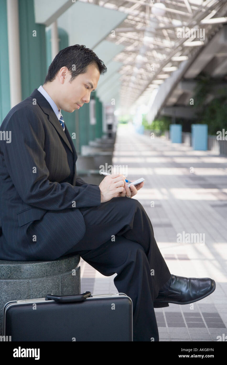 Side profile of a businessman sitting and using a hand held device - Stock Image