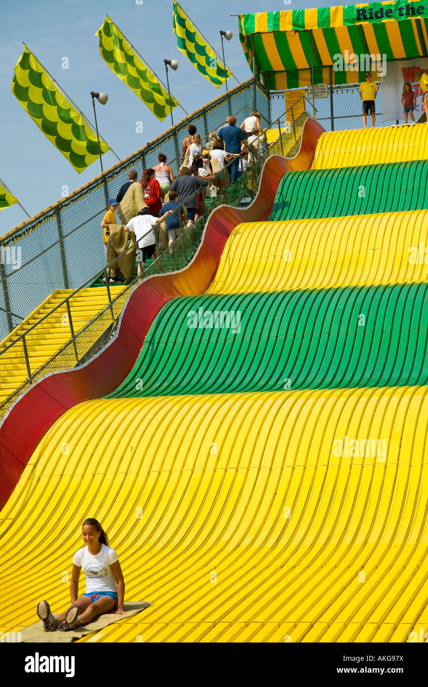 WISCONSIN Milwaukee Children and adults ride burlap sacks down giant slide green and yellow with waves people on - Stock Image