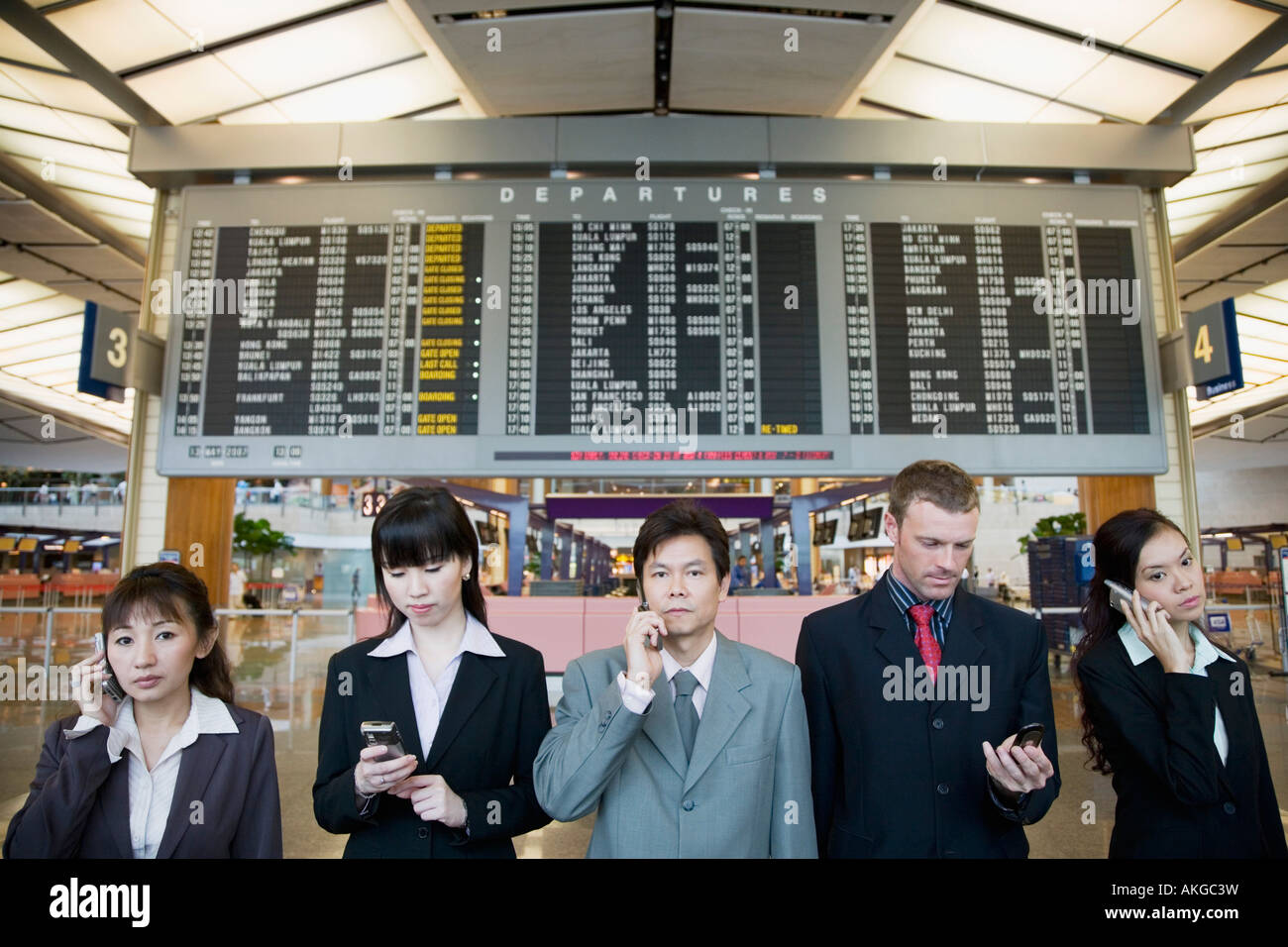 Five business executives standing in front of an arrival departure board at an airport - Stock Image
