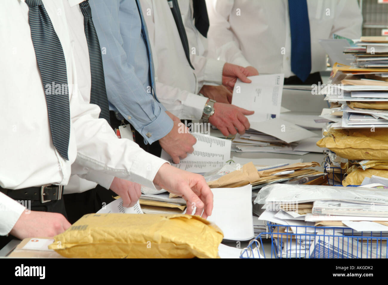 Men opening and sorting mail in the postroom of an office Stock ...