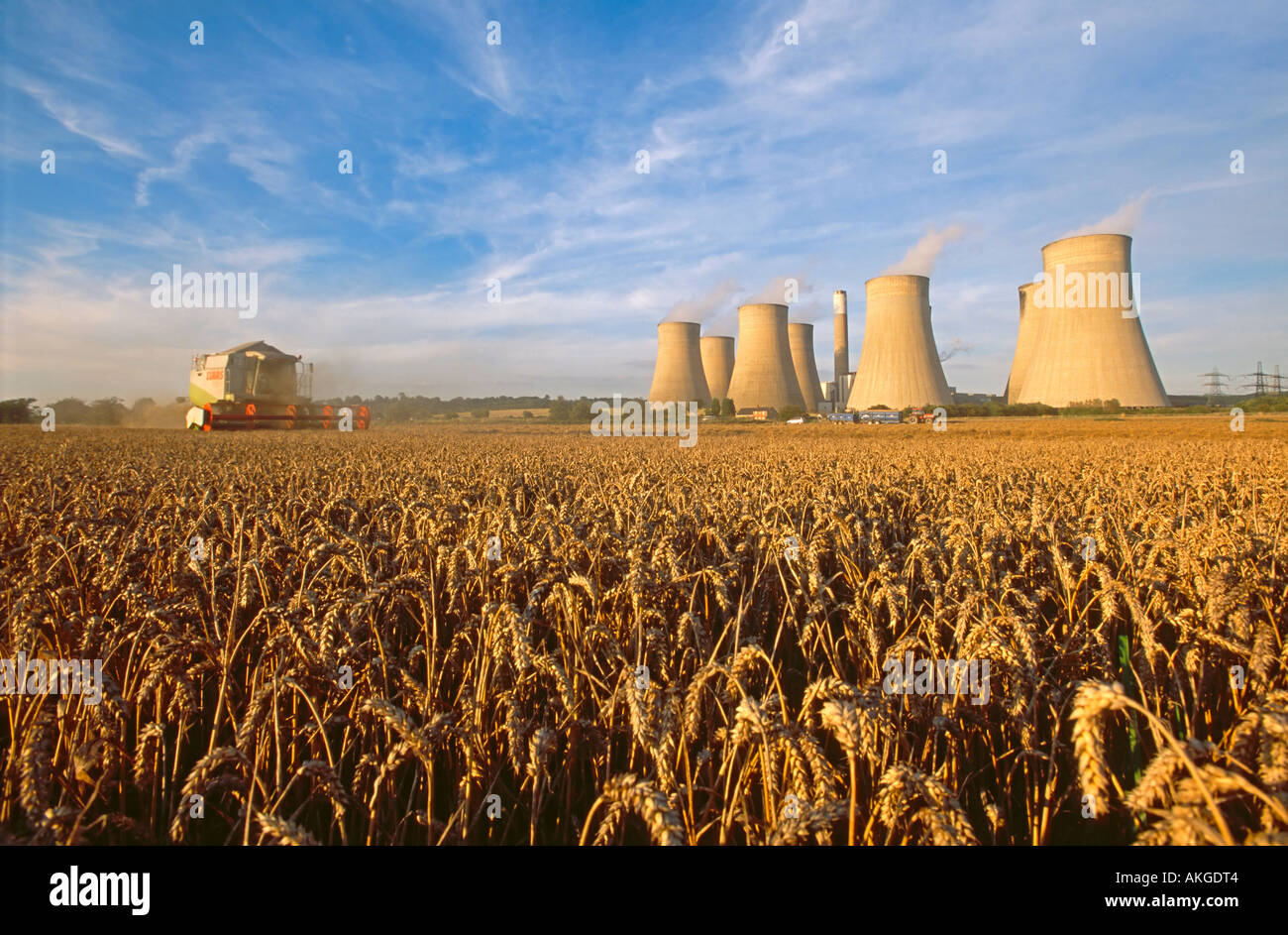 A combine harvester harvesting a wheat crop with Ratcliffe on Sour coal fired power station behind. - Stock Image