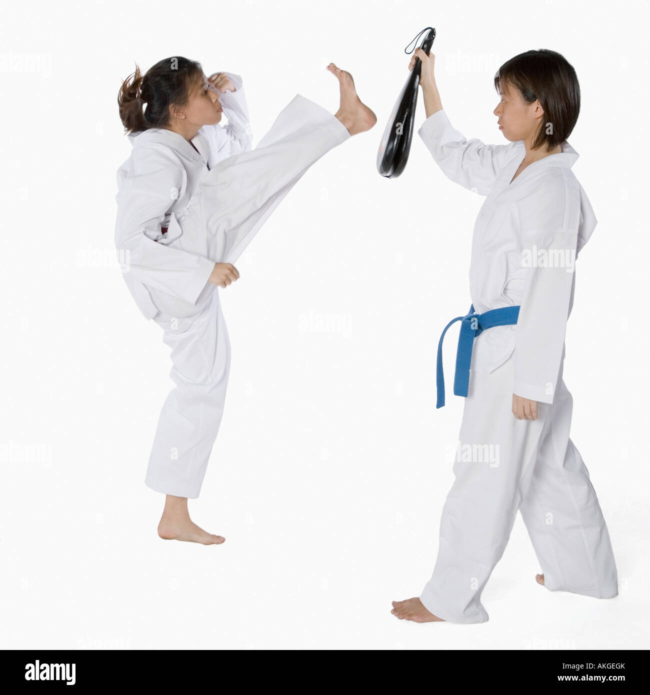 Side profile of two young women practicing karate - Stock Image