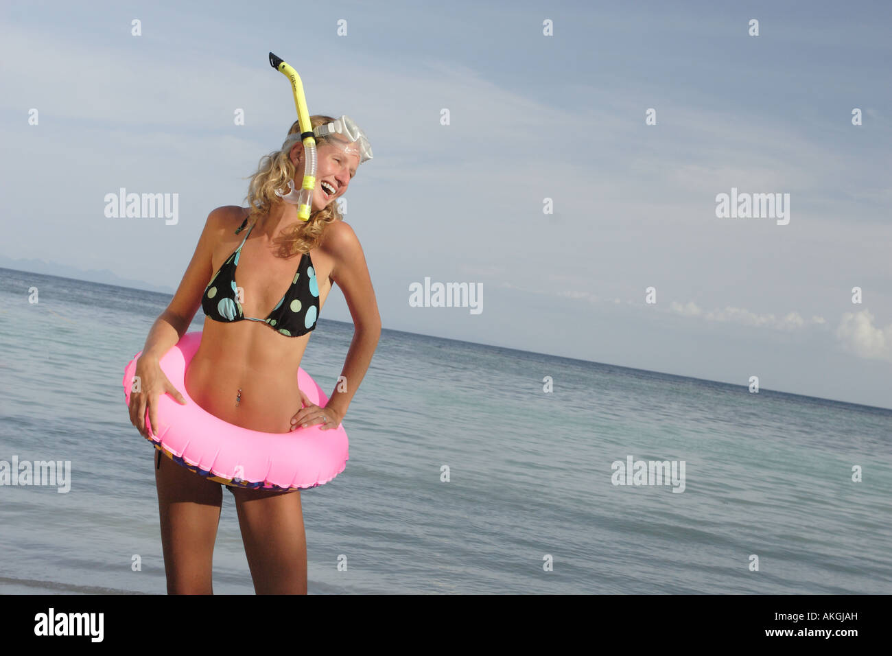 Woman in a bikini on the beach laughing with a snorkel, mask and inflatable ring. - Stock Image