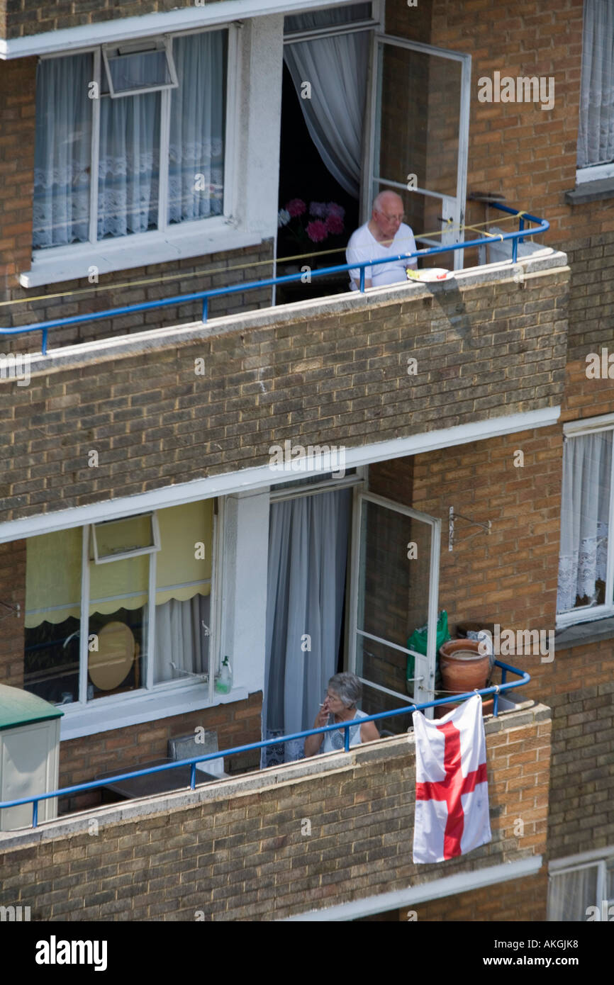 Elderly people on the balcony of a council estate on a hot summer day London England Britain uk - Stock Image