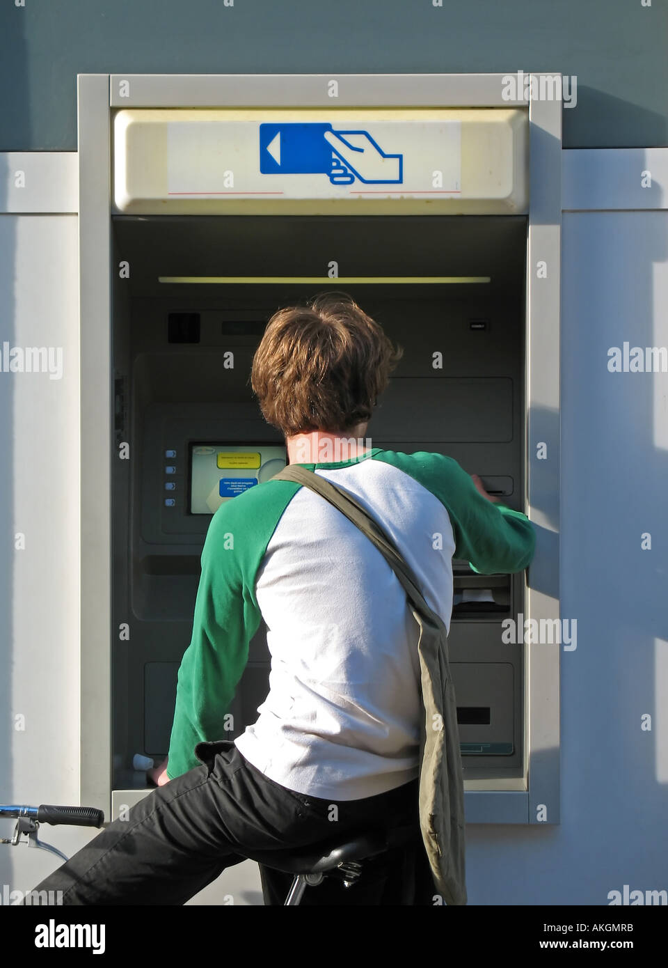 Rear view of a young man withdrawing cash at bank's ATM, Colmar, Alsace, France Stock Photo
