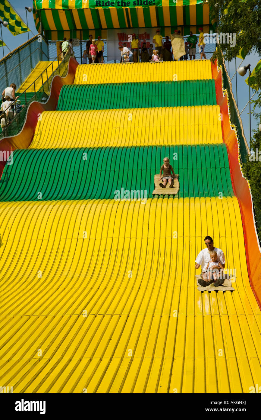 WISCONSIN Milwaukee Children and adults ride burlap sacks down giant slide green and yellow with waves - Stock Image