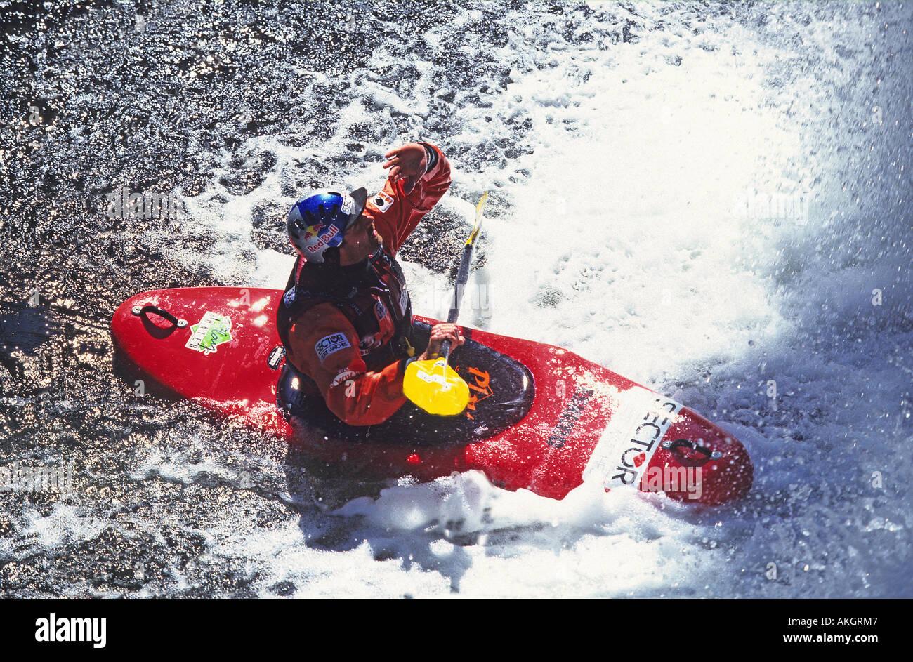 Shaun Baker kayaking under a waterfall - Stock Image