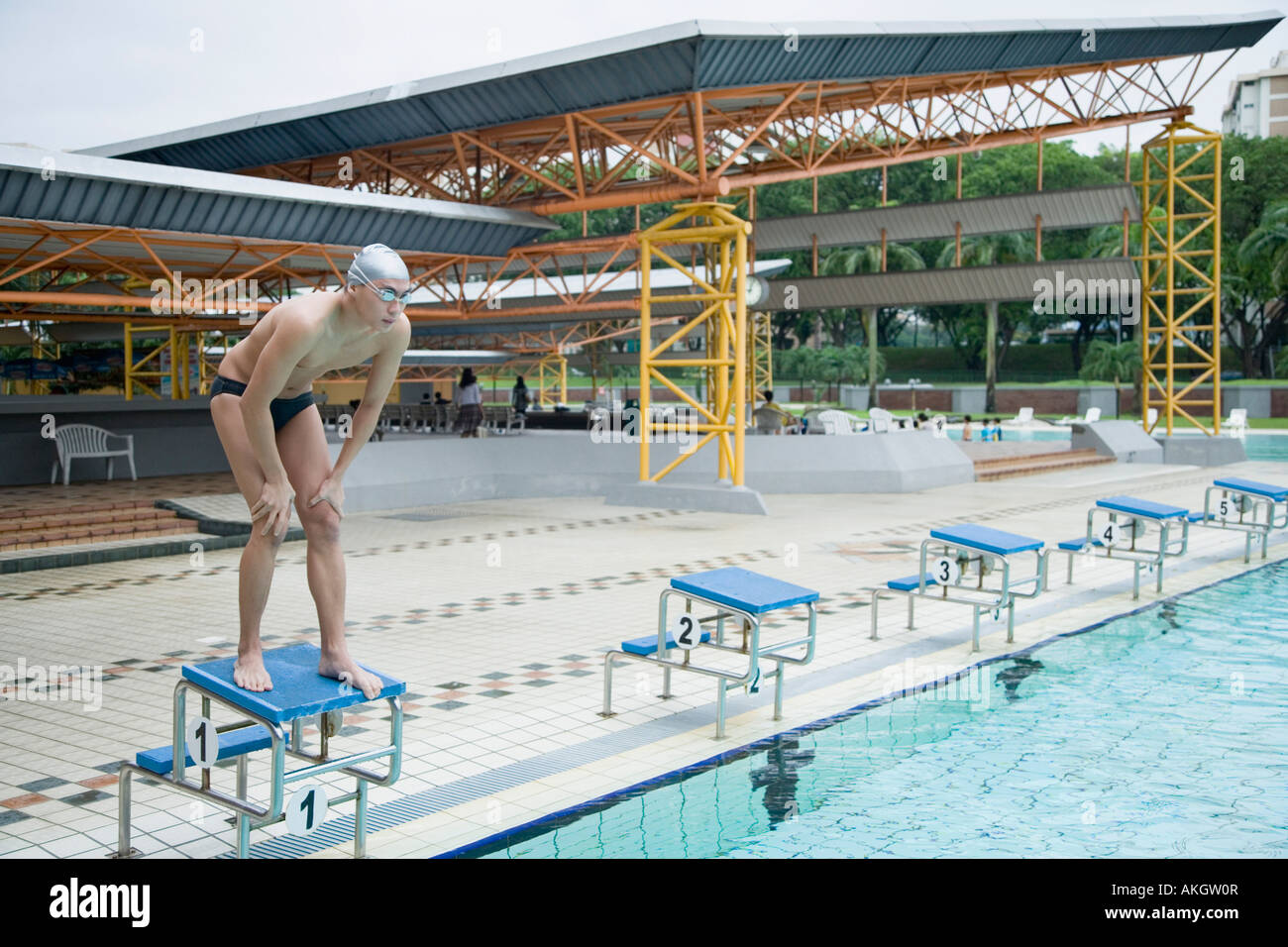 Young man standing on a starting block - Stock Image
