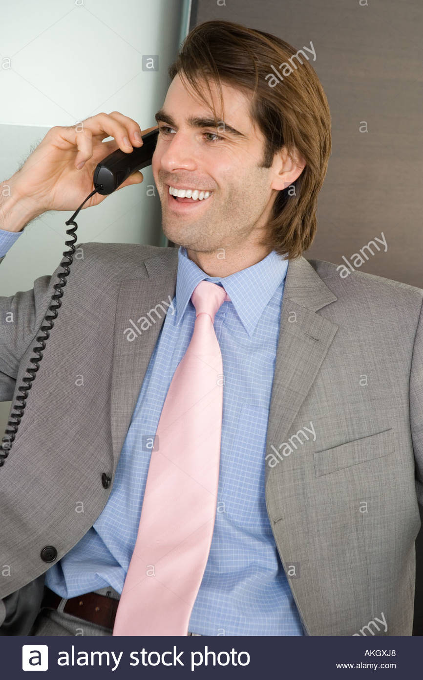 Man in full suit talking on phone - Stock Image
