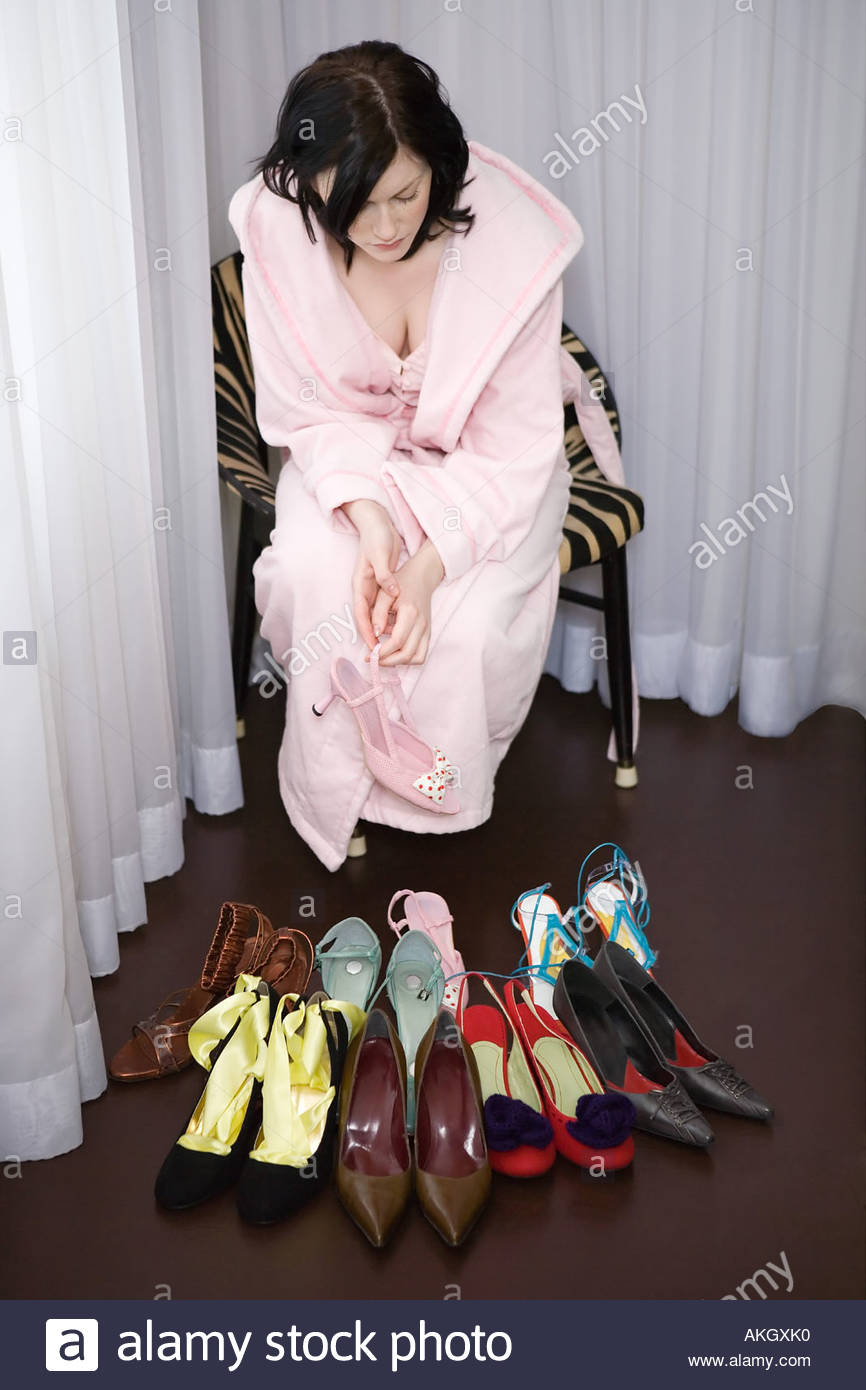 Woman in bathrobe looking at shoes collection - Stock Image
