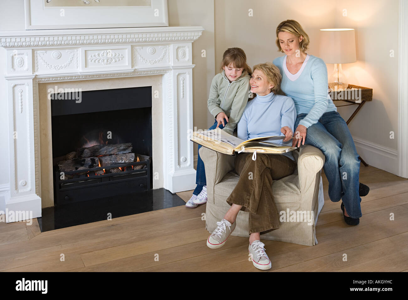 Female relatives looking at photograph album - Stock Image