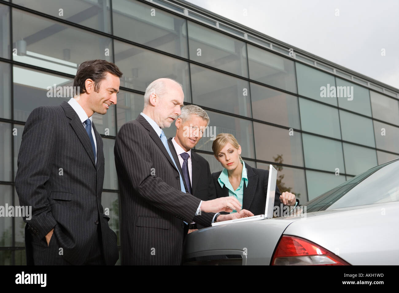 Businesspeople looking at laptop on automobile boot - Stock Image