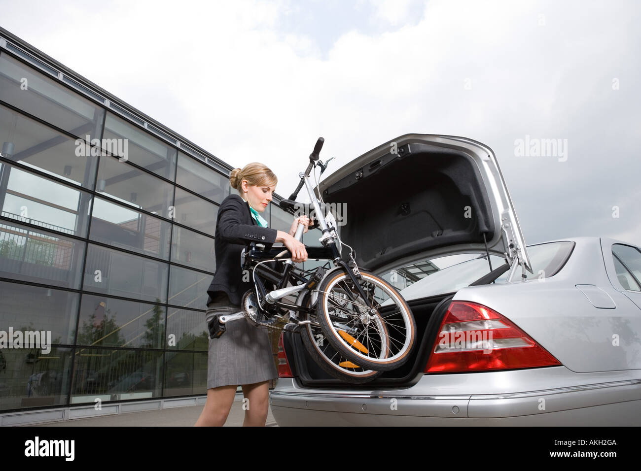 Businesswoman putting folded bicycle in car boot - Stock Image