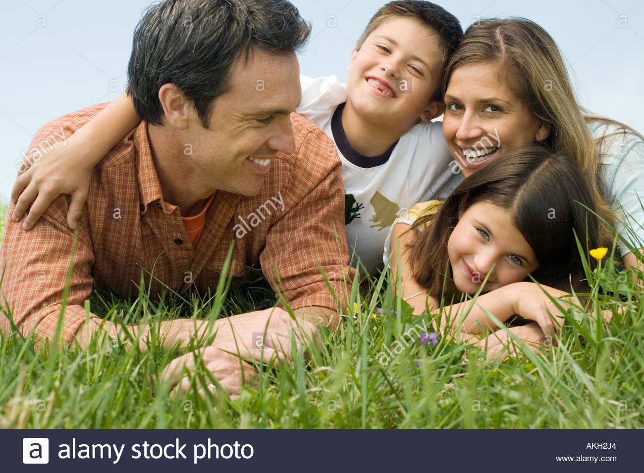 Family lying on meadow - Stock Image