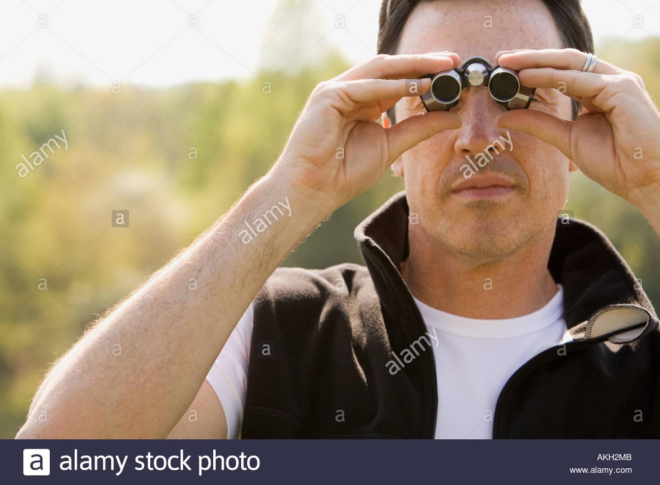 Man looking through binoculars - Stock Image