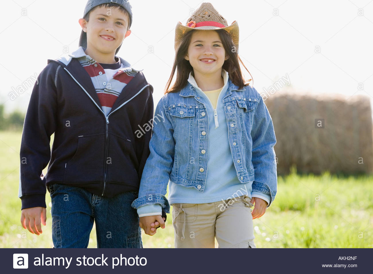 Boy and girl walking on meadow, holding hands - Stock Image